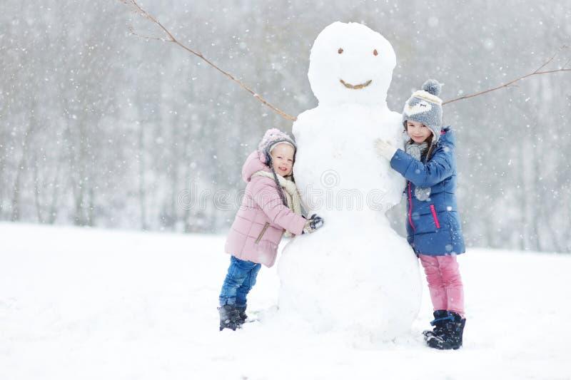 Twee grappige aanbiddelijke kleine zusters in de winterpark royalty-vrije stock afbeelding