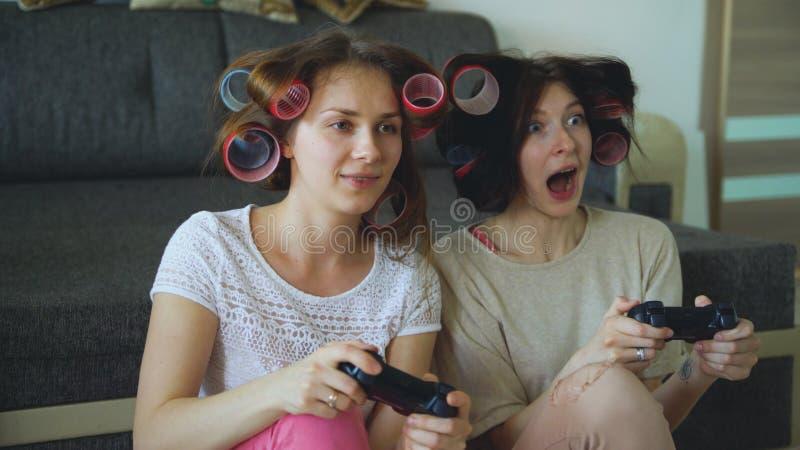 Twee grappige de consolespelen van het vrouwenspel met gamepad en hebben thuis pret royalty-vrije stock foto's
