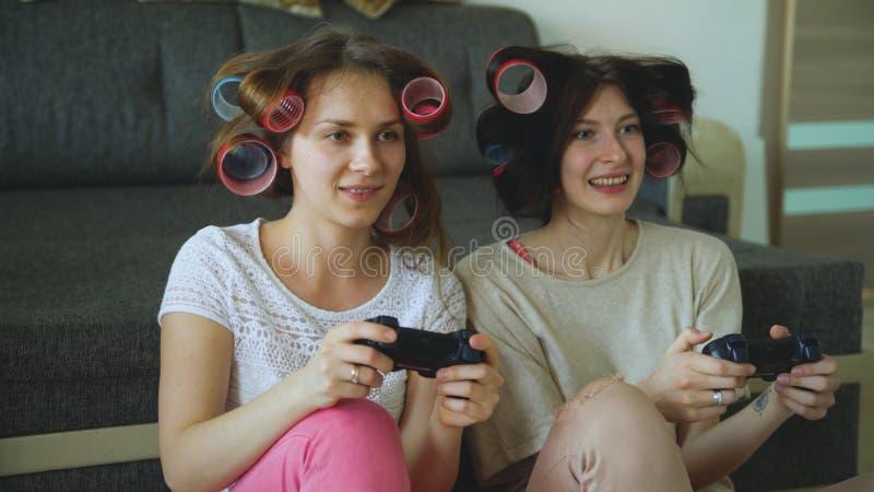 Twee grappige de consolespelen van het vrouwenspel met gamepad en hebben thuis pret stock afbeelding