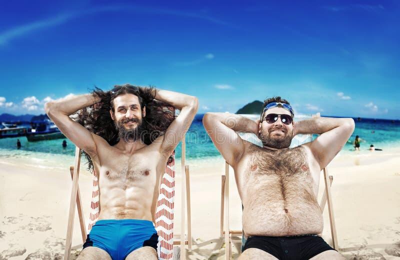 Twee grappige kerels die op het strand rusten stock afbeelding