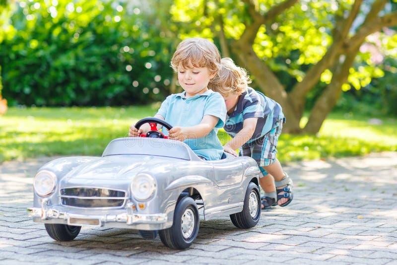 Twee grappige kleine vrienden die met grote oude stuk speelgoed auto spelen royalty-vrije stock foto