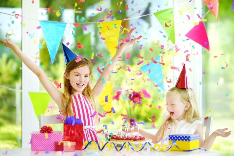 Twee grappige kleine zusters die verjaardagspartij hebben die thuis, kaarsen op verjaardagscake blazen royalty-vrije stock afbeelding