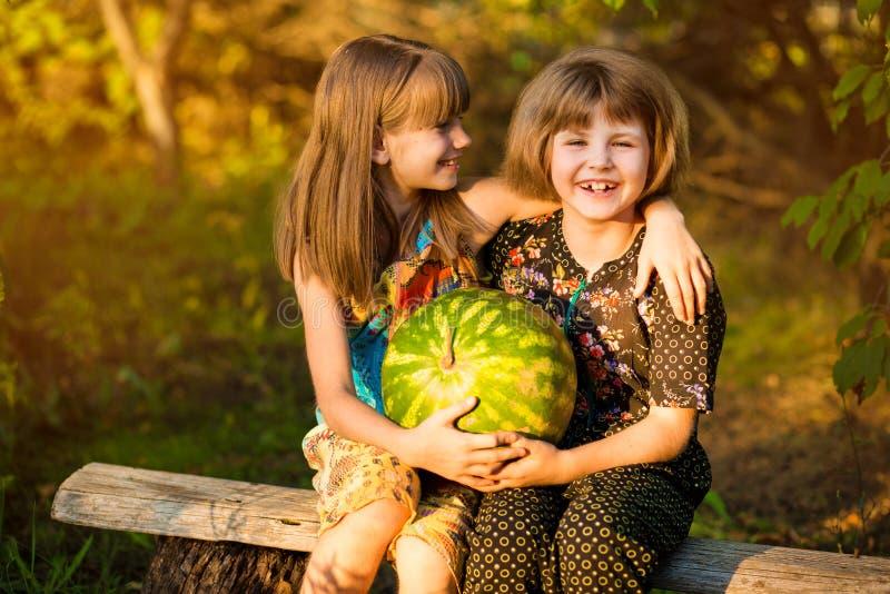 Twee grappige kleine zusters die watermeloen in openlucht op warme en zonnige de zomerdag eten Gezonde natuurvoeding stock foto