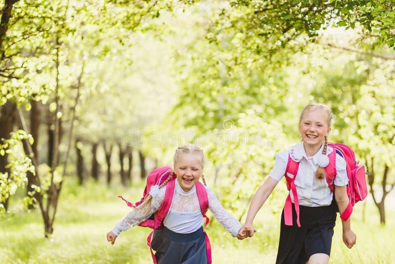 Twee grappige schoolmeisjes die holdingshanden in werking stellen openlucht royalty-vrije stock foto's