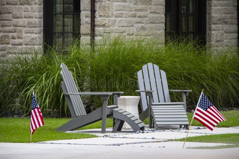 Twee grijze Adirondack zitten het zitten op een klein terras met lijst tussen hen voor lang decoratief gras en vensters van rots  royalty-vrije stock foto
