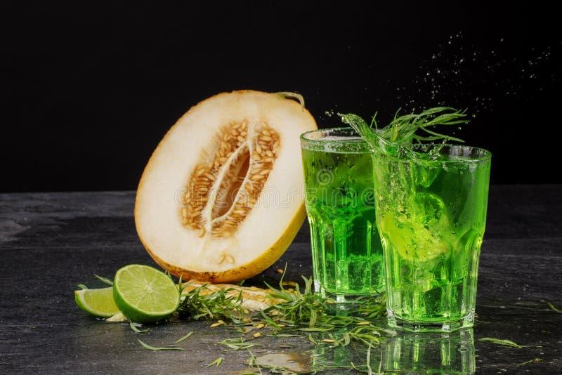 Twee groene alcoholcocktails op een zwarte achtergrond Dranken met dragon, ijsblokjes, besnoeiings sappige meloen, en zure kalk D stock afbeeldingen