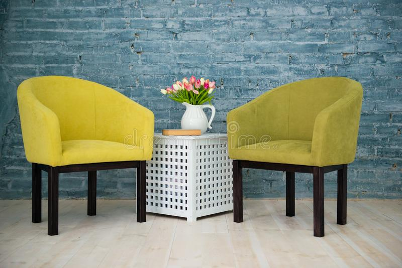 Twee groene stoelen op de achtergrond van een grijze bakstenen muur Binnenlands stock foto