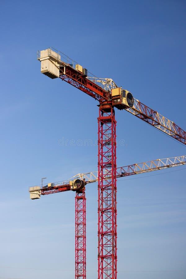 Twee grote kraanbalkkranen tegen een wolkenloze blauwe hemel bij de bouwwerf van een grote recreatie complex in de stad van royalty-vrije stock foto's