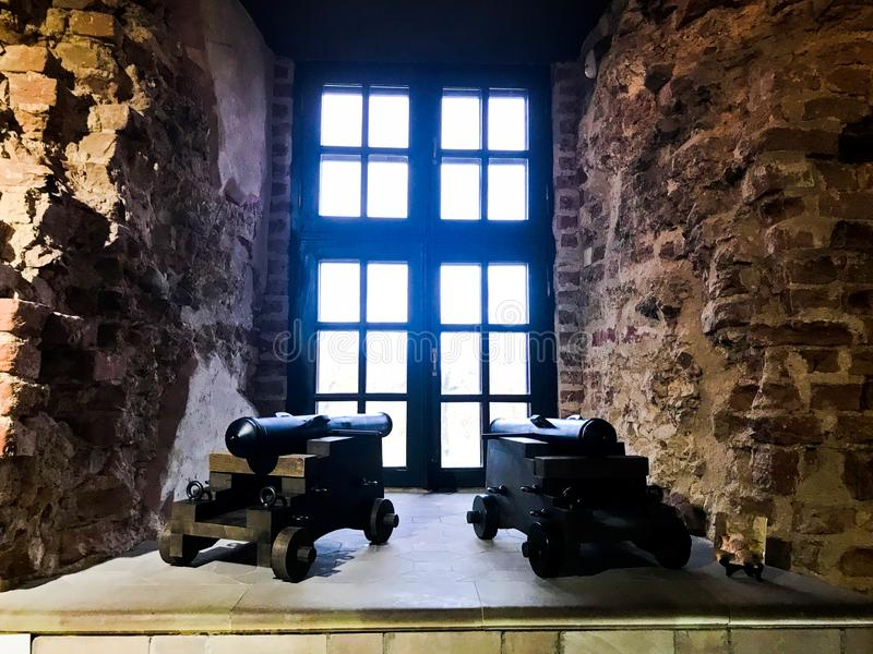 Twee grote krachtige oude middeleeuwse kanonnen die het venster onder ogen zien royalty-vrije stock afbeeldingen
