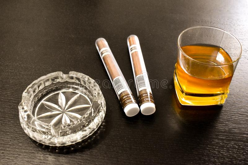 Twee grote sigaren, een kristalasbakje en een glas wisky op de zwarte lijst Boekarest, Roemenië - 03 04 2019 royalty-vrije stock fotografie