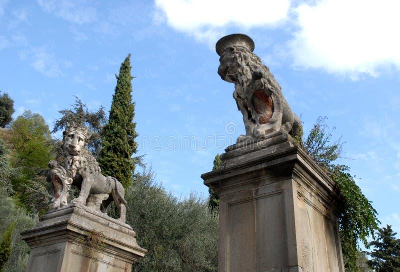 Twee grote standbeelden van leeuwen met een kroon op zijn hoofd door de heuvels in Veneto (Italië) stock fotografie