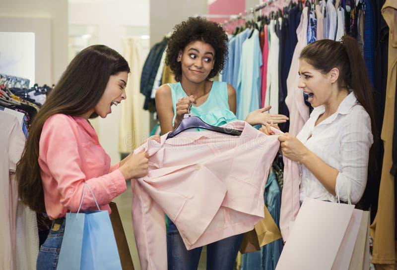 Twee gulzige meisjes die voor jasje in warenhuis vechten stock afbeelding