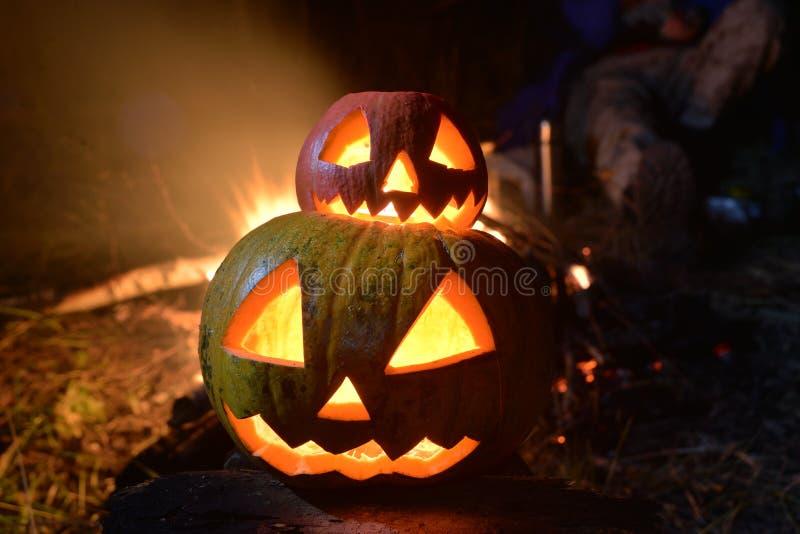 Twee Halloween-pompoenen vijzelen gezichten in het donkere bos op royalty-vrije stock foto's
