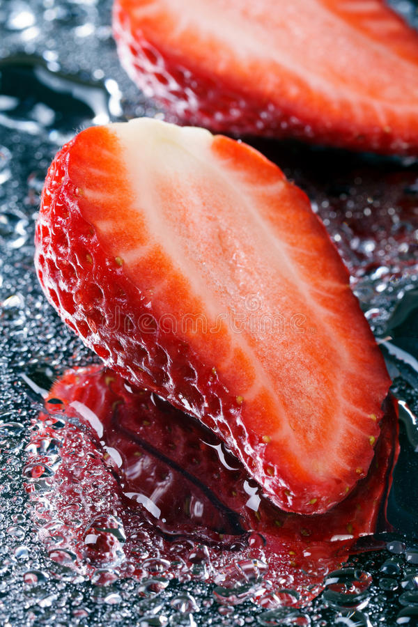 Twee halve verse aardbeien met watermacro stock fotografie