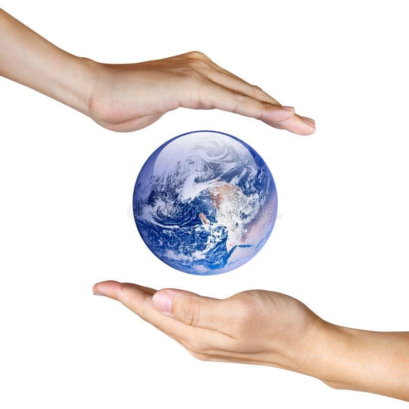 Twee handen die de aarde bewaren stock foto