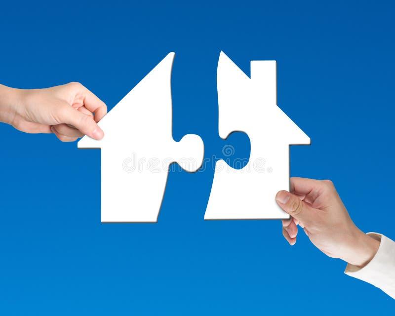 Twee handen die figuurzaagstukken houden om het raadsel van de huisvorm te beëindigen royalty-vrije stock afbeelding