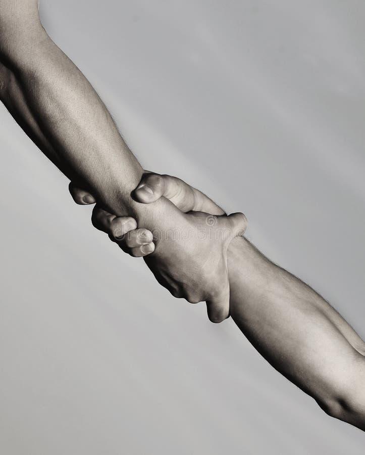 Twee handen, die hand van een vriend helpen Redding, die gebaar of handen helpen Sterke greep Handdruk, wapens, vriendschap stock foto