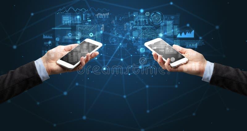 Twee handen die smartphones aan synchronisatie bedrijfsgegevens houden stock afbeelding