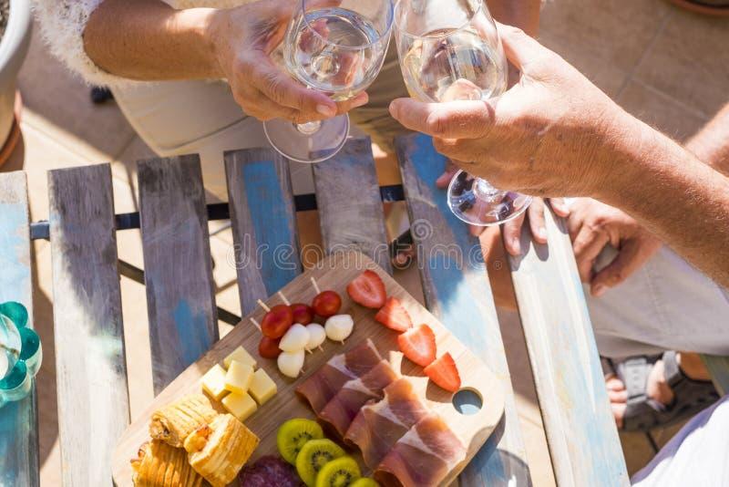 Twee handen hogere dichte omhoog het drinken wijn met sommige vruchten op stock fotografie