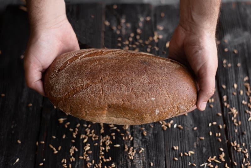 Twee handen houden een brood van donker roggebrood op een donkere achtergrond stock afbeelding