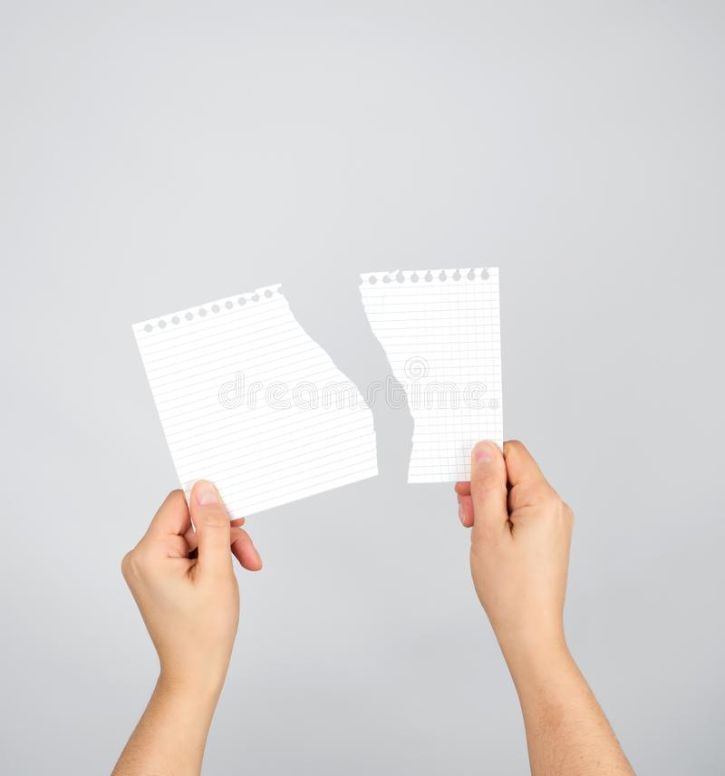twee handen houden een gescheurd stuk van document op een grijze achtergrond royalty-vrije stock afbeelding