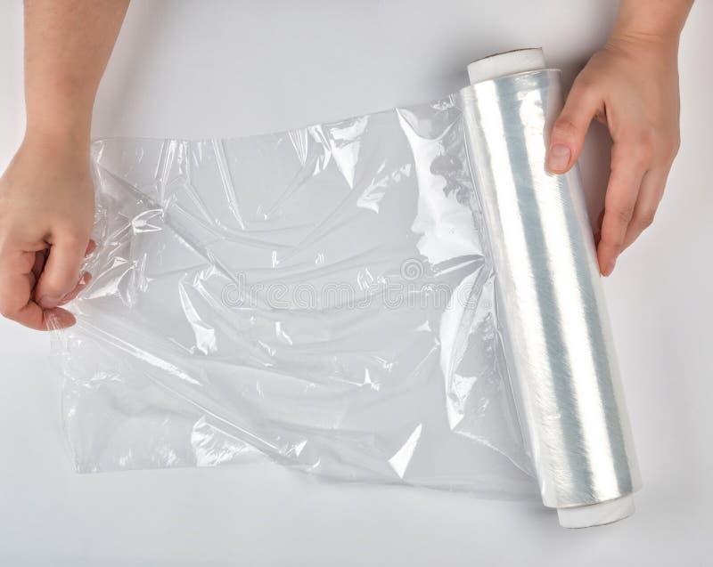 twee handen houden een groot broodje van gekronkelde witte transparante film voor het verpakken van voedsel stock afbeelding