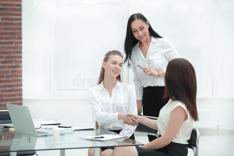 Twee handen van de bedrijfsvrouwenschok met elkaar boven het ondertekende contract royalty-vrije stock afbeelding