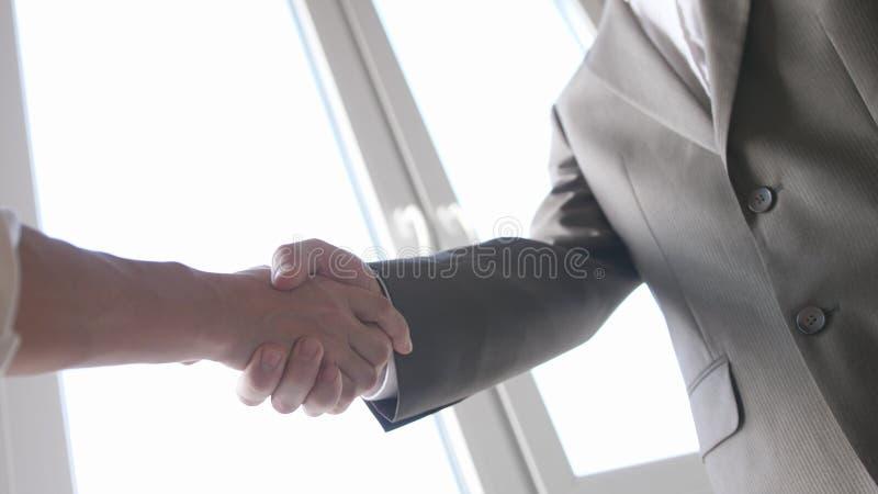 Twee handen van de partnerschok wanneer het samenkomen tussen een man en een vrouw in kostuum Succesvolle overeenkomst royalty-vrije stock foto's