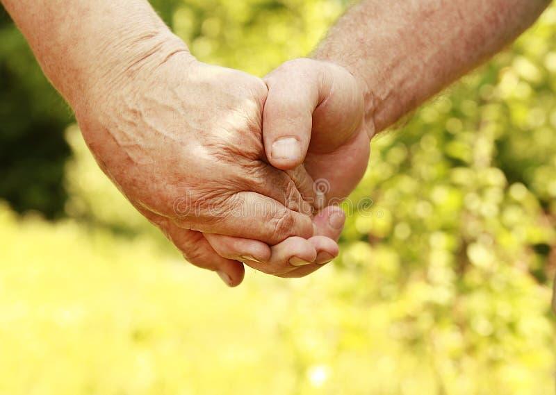 Twee handen van een bejaard paar stock afbeelding