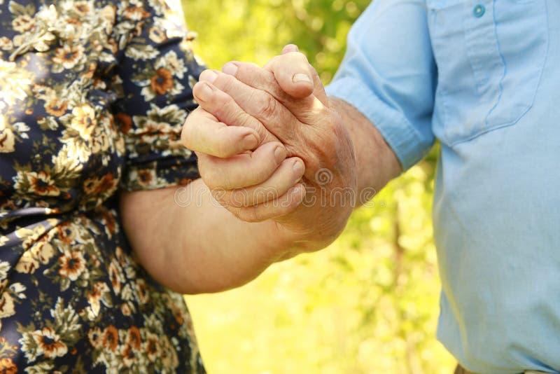 Twee handen van een bejaard paar in liefde stock afbeeldingen