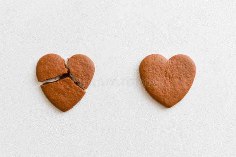 Twee hart gevormde koekjes, één van hen is gebroken op een witte achtergrond Barst hart-vormige koekjes als concept het breken en stock foto