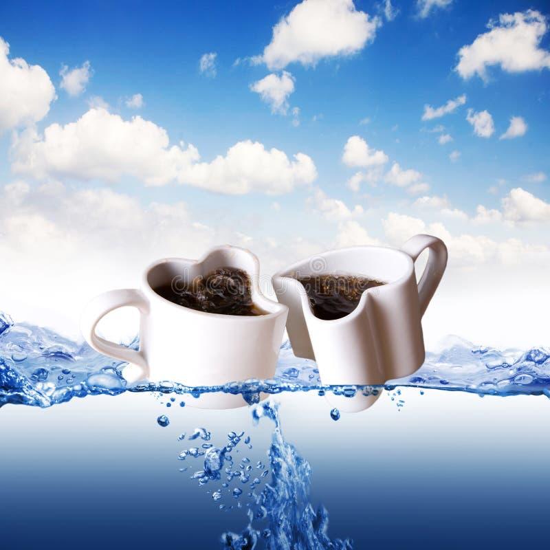 Twee hart gevormde koppen van koffie in een water stock fotografie