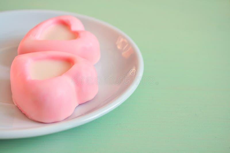Twee hart-vormige roze soufflécakes die op het wit liggen plateren op de groene houten lijst Selectieve zachte nadruk op de cake  stock afbeeldingen