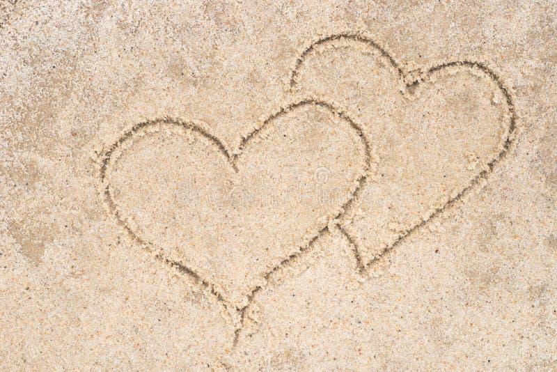 Twee harten die in zand trekken stock fotografie