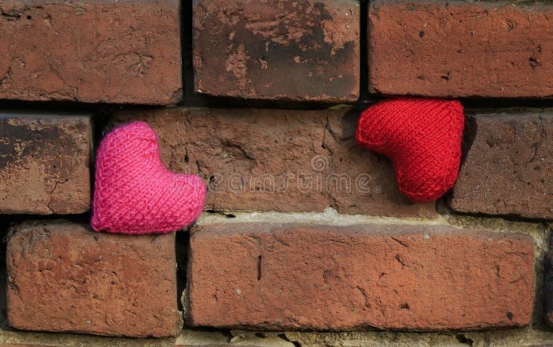 Twee harten in het rode en roze hangen op afbrokkelende oude geweven B stock foto's