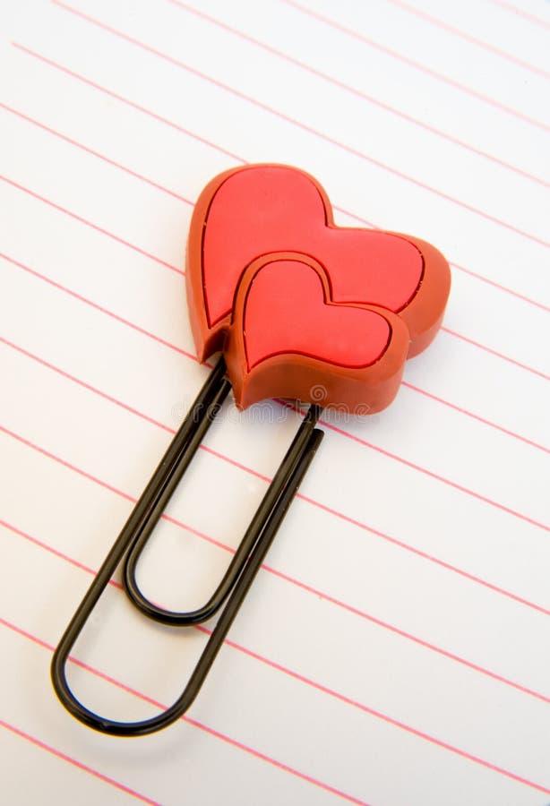 Twee harten op een paperclip op gevoerd notadocument. royalty-vrije stock fotografie