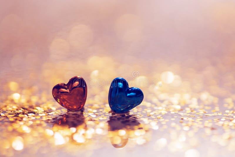 Twee harten zijn rood en blauw op de achtergrond van een bokeh van lovertjes De dag van de valentijnskaart `s royalty-vrije stock fotografie