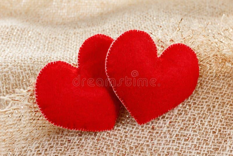 Twee hartensymbool van liefde op juteachtergrond royalty-vrije stock foto's