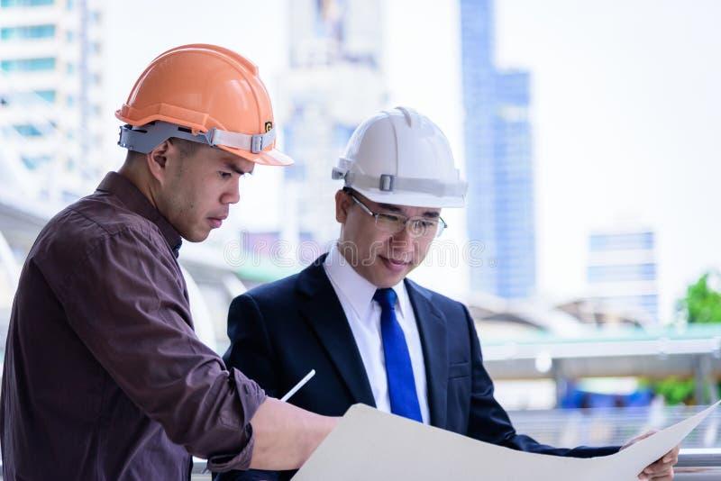 Twee heeft de Aziatische bedrijfs en ingenieursmens planning en het werken voor royalty-vrije stock foto's