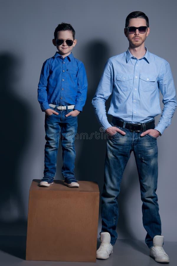 Twee heren: jonge vader en zijn kleine leuke zoon in zonnebril Zijn gekleed in overhemden en jeans Dit is dossier van EPS10-forma stock afbeeldingen