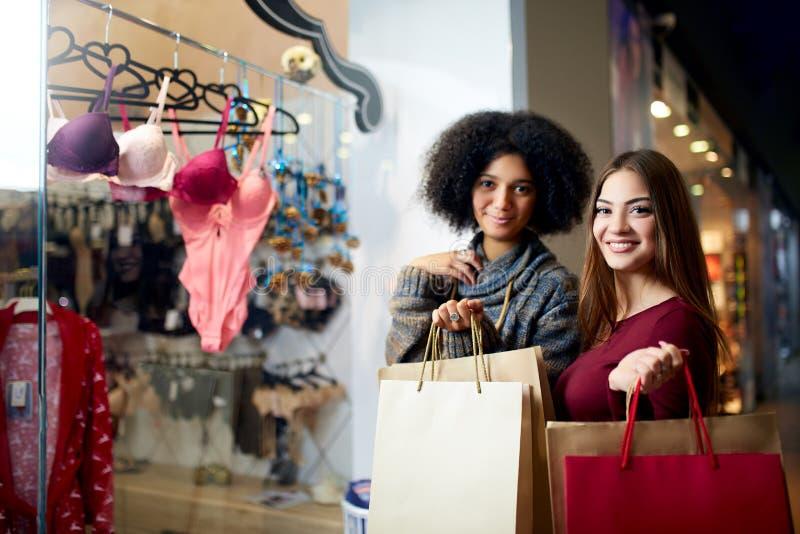 Twee het gelukkige multi-etnische jonge gemengde rasvrouw besluit winkelen voor lingerie dichtbij de winkelvenster van de kleding royalty-vrije stock afbeeldingen