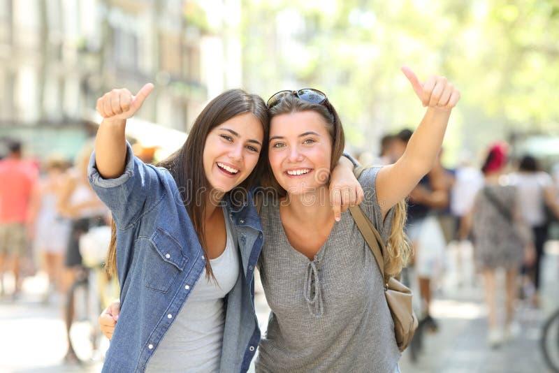 Twee het gelukkige vrienden beduimelt gesturing omhoog samen royalty-vrije stock afbeeldingen
