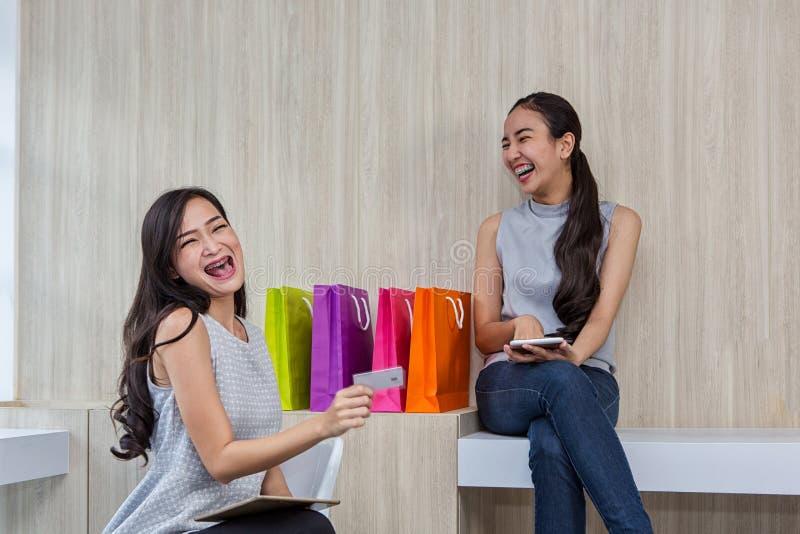Twee het gelukkige vrouwen gebruiken die op mobiele telefoon en tablet winkelen Twee jonge vrouwen die het winkelen glimlachen Wi stock afbeelding