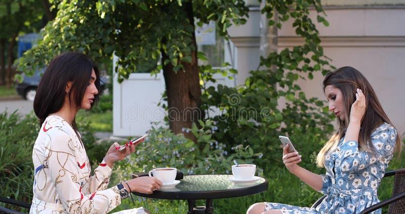 Twee het gelukkige vrouwenvriend snakt genieten die koffie in openlucht middelgrote koffie drinken schot stock afbeelding