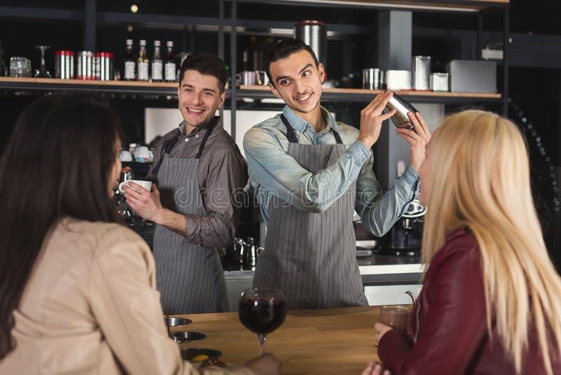 Twee het glimlachen baristas die tot koffie maken aan klanten stock fotografie