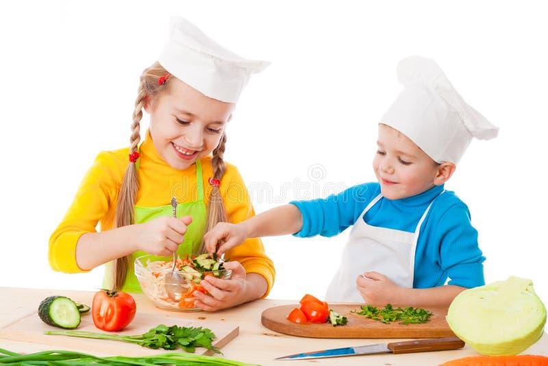 Twee het glimlachen jonge geitjes die salade mengen stock fotografie