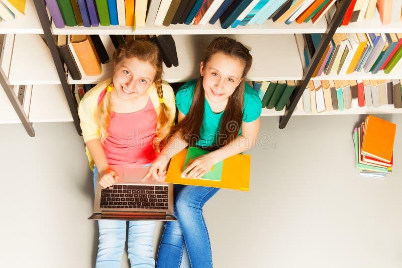 Twee het glimlachen meisjesportret van hierboven in bibliotheek stock foto's