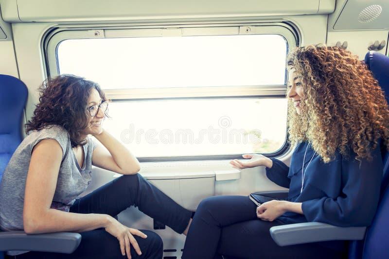 Twee het glimlachen mooie meisjesbespreking aan elkaar stock foto's