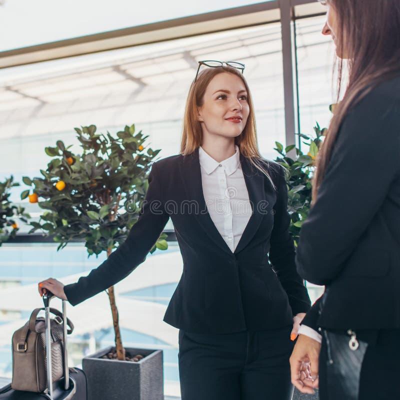Twee het glimlachen partners spreken die zich in luchthaven bevinden royalty-vrije stock afbeelding
