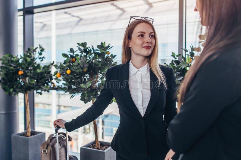 Twee het glimlachen partners spreken die zich in luchthaven bevinden stock afbeelding
